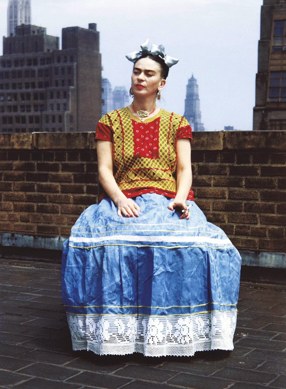 Kahlo sitting regal in her huipil, skirt, and headpiece.